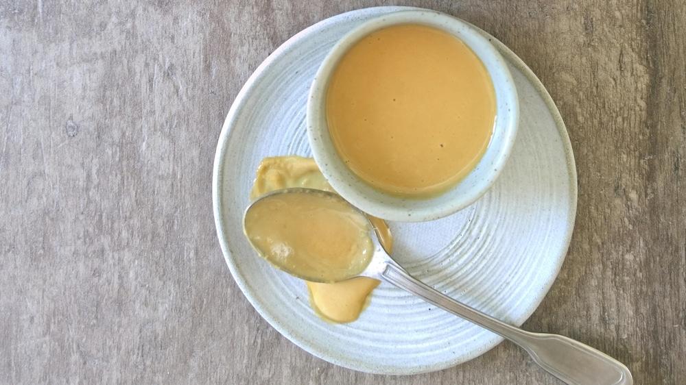 Un grand contenant de sauce tahini avec un petit bol de sauce et une cuillère.