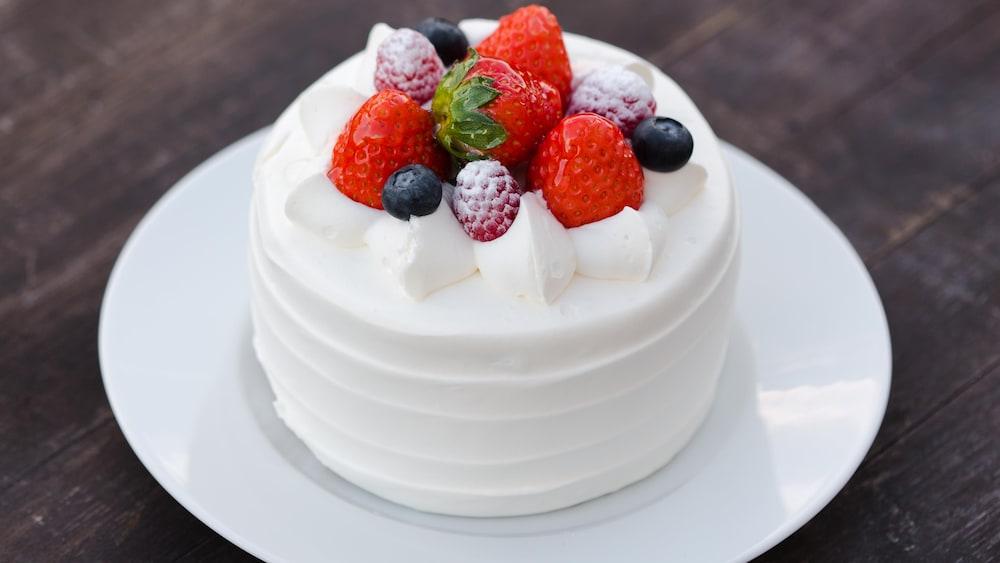 Un petit gâteau recouvert de crémage blanc et de petits fruits.