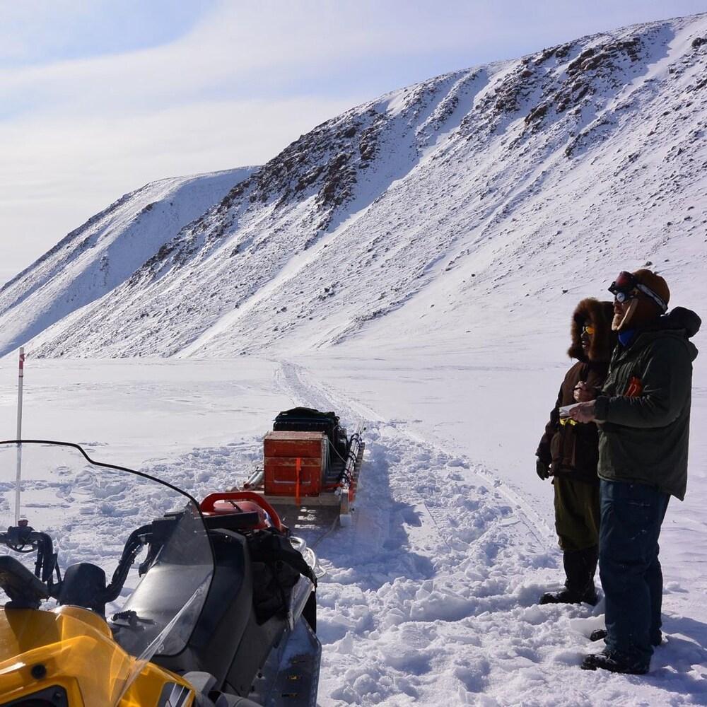 Deux chercheurs à côté d'une motoneige tirant un traîneau avec du matériel.