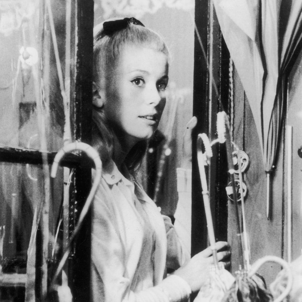 Catherine Deneuve dans l'embrasure d'une fenêtre sur cette photo tirée du film <i>Les parapluies de Cherbourg</i>.