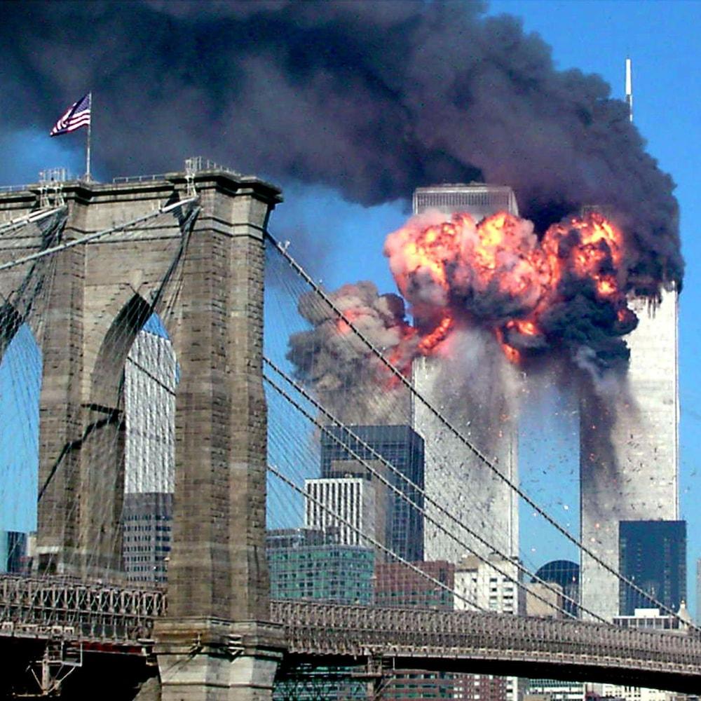 On voit l'énorme explosion provoquée par l'impact entre l'avion et l'une des tours jumelles. Au premier plan, le pont de Brooklyn.