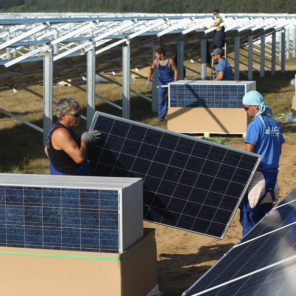 Des travailleurs installent des panneaux solaires en Allemagne, au milieu d'un champ.