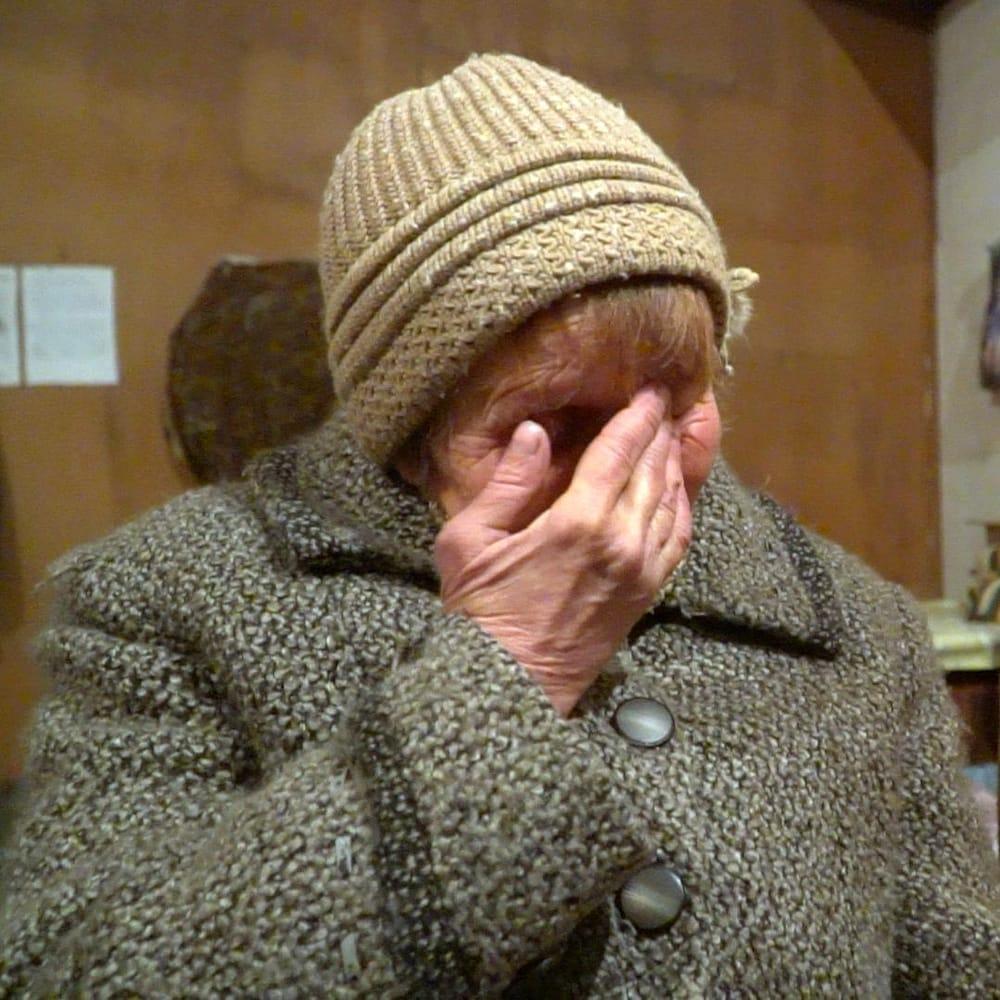 Ludmila, la main sur le visage, pleure.