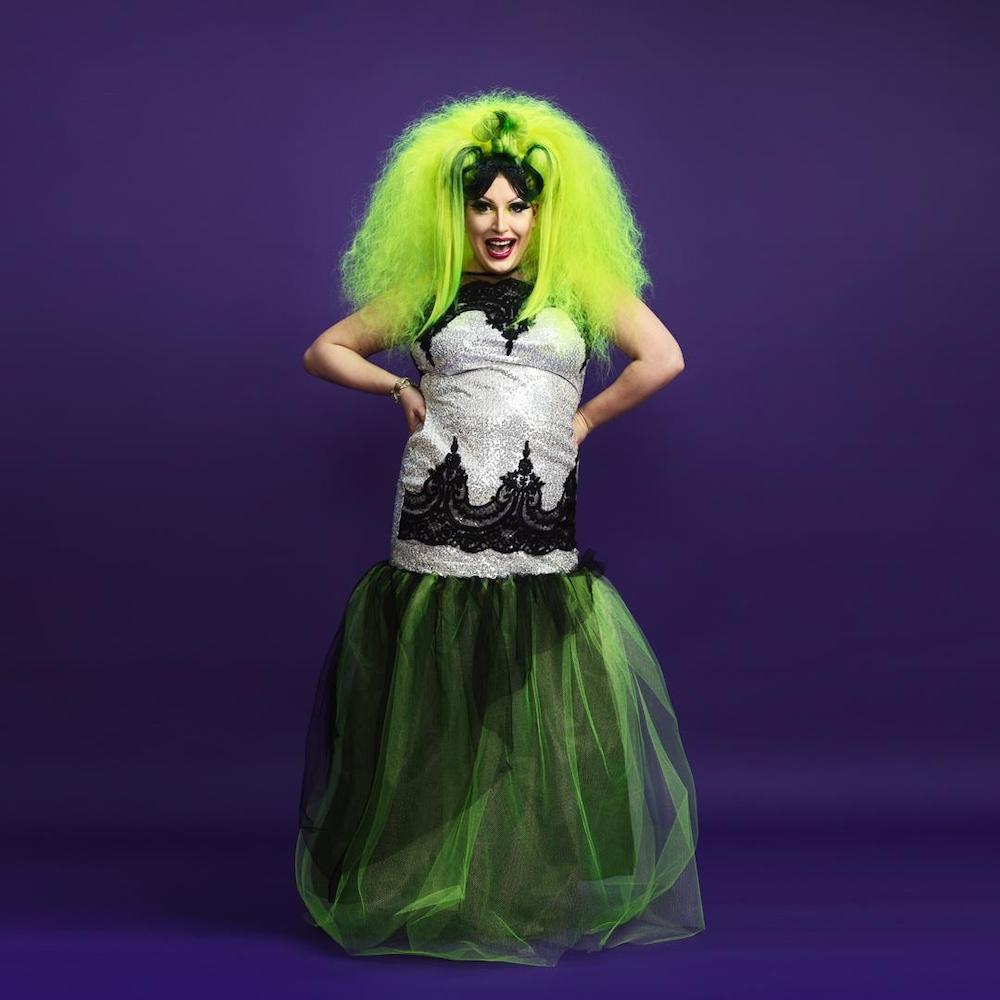 Une drag queen porte une longue robe de bal argentée avec un tulle et une perruque vert néon. En regardant la caméra, elle a le sourire large et les mains sur les hanches.