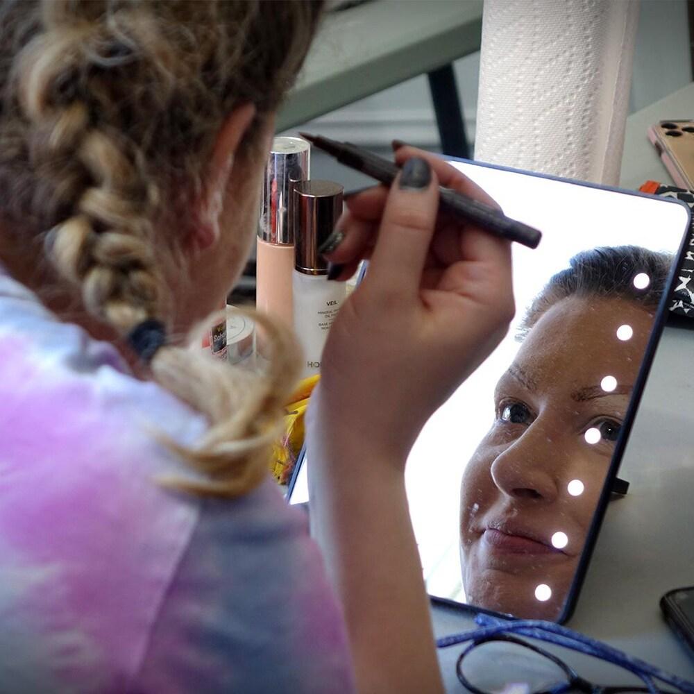 Réflexion du visage souriant d'Annabelle qui se maquille dans un miroir.