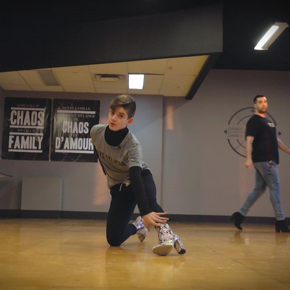 Dans un studio de danse, un jeune danse en talons hauts, alors que son professeur, en talons aussi, le regarde.