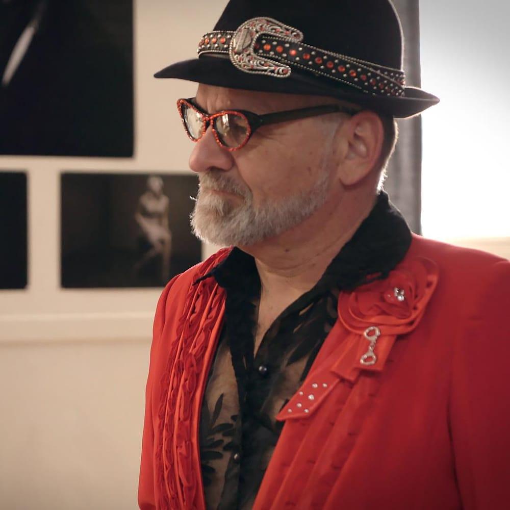 Un homme avec la barbe grise porte un chapeau fedora et des lunettes aux accents rouge. Il est debout dans un studio de photographie.