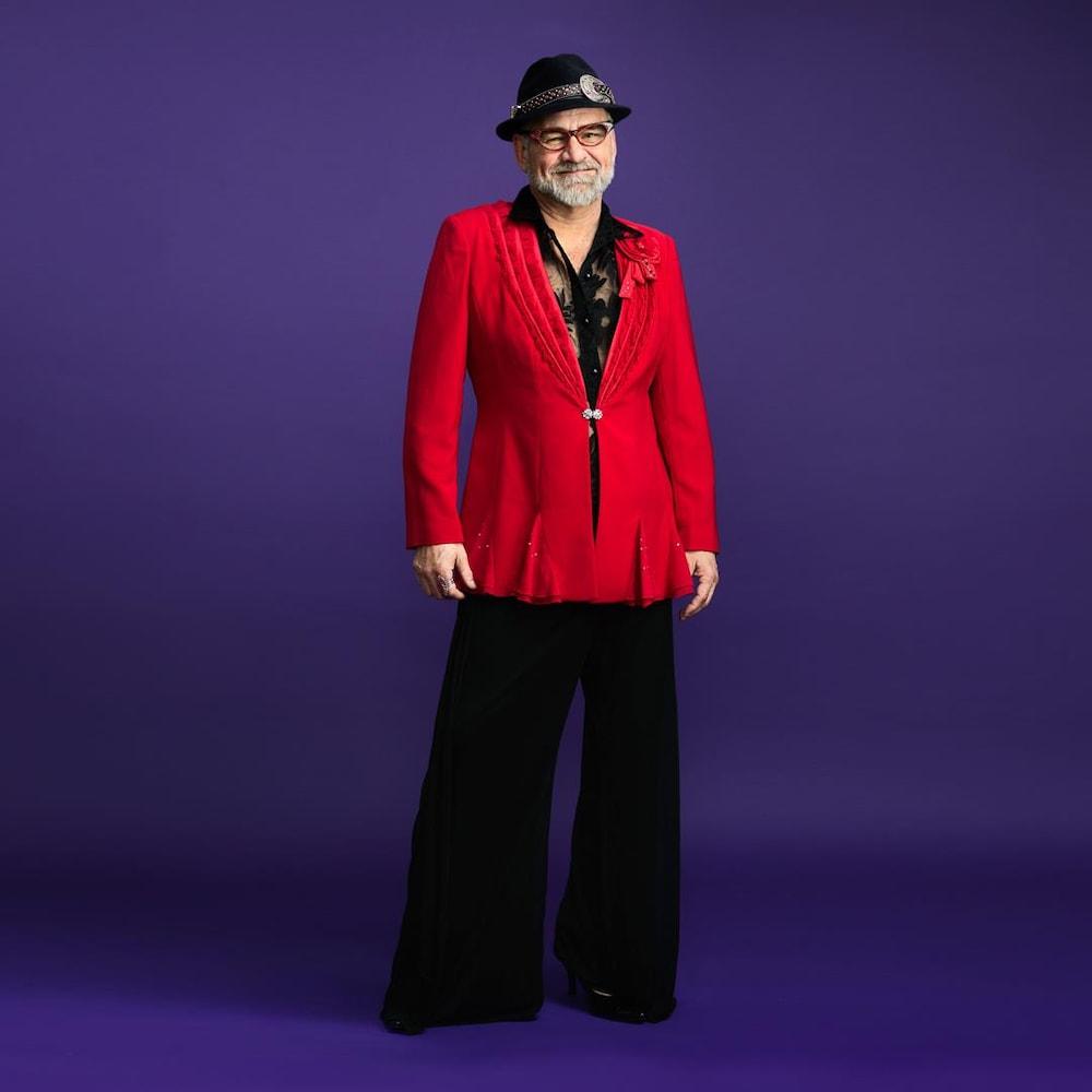 Un homme barbu, âgé d'environ 50 ans, porte un pantalon noir à jambes amples avec un veston féminin rouge. Avec un chapeau fedora noir avec accents argentés, il sourit en regardant la caméra.