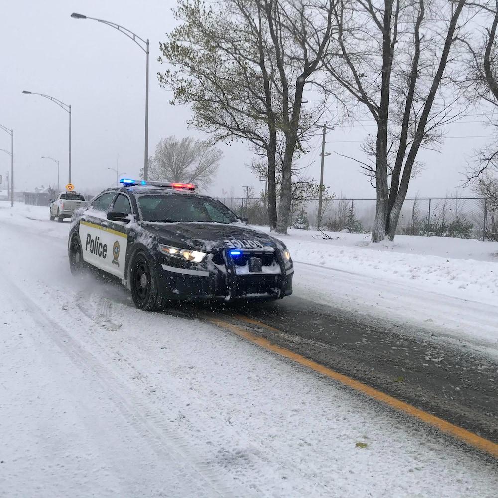 Une voiture de police sur une route enneigée.