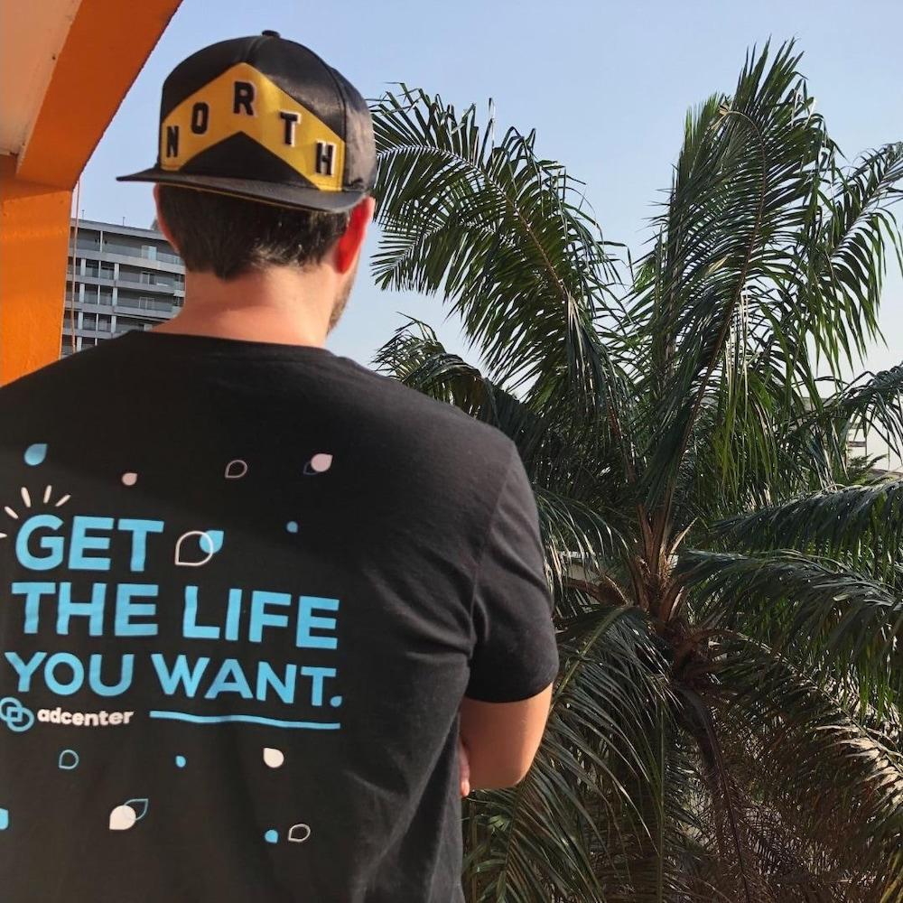 Un homme regarde un palmier en portant un t-shirt AdCenter.