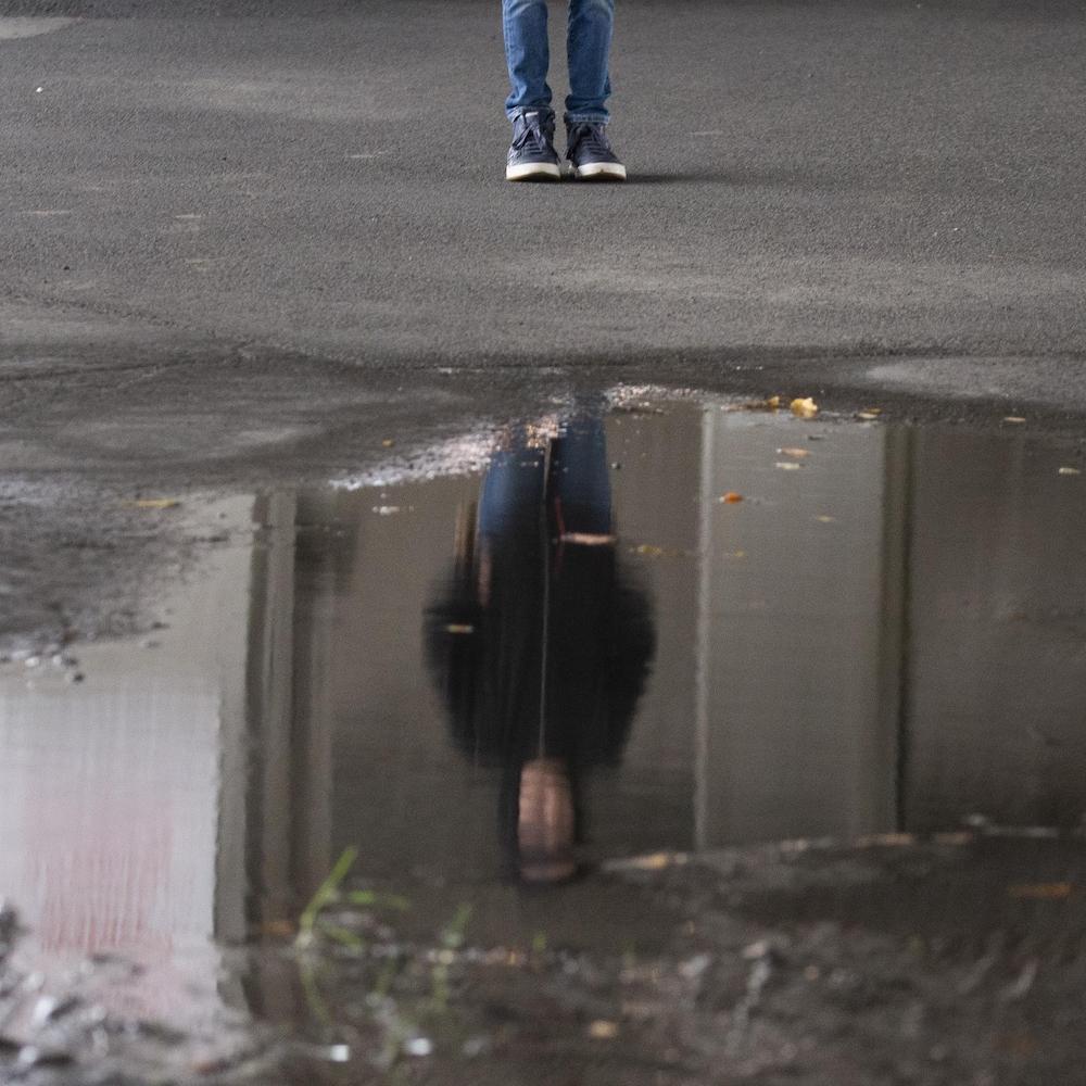 Un jeune adolescent debout dans un stationnement voit son image reflétée dans une flaque d'eau.