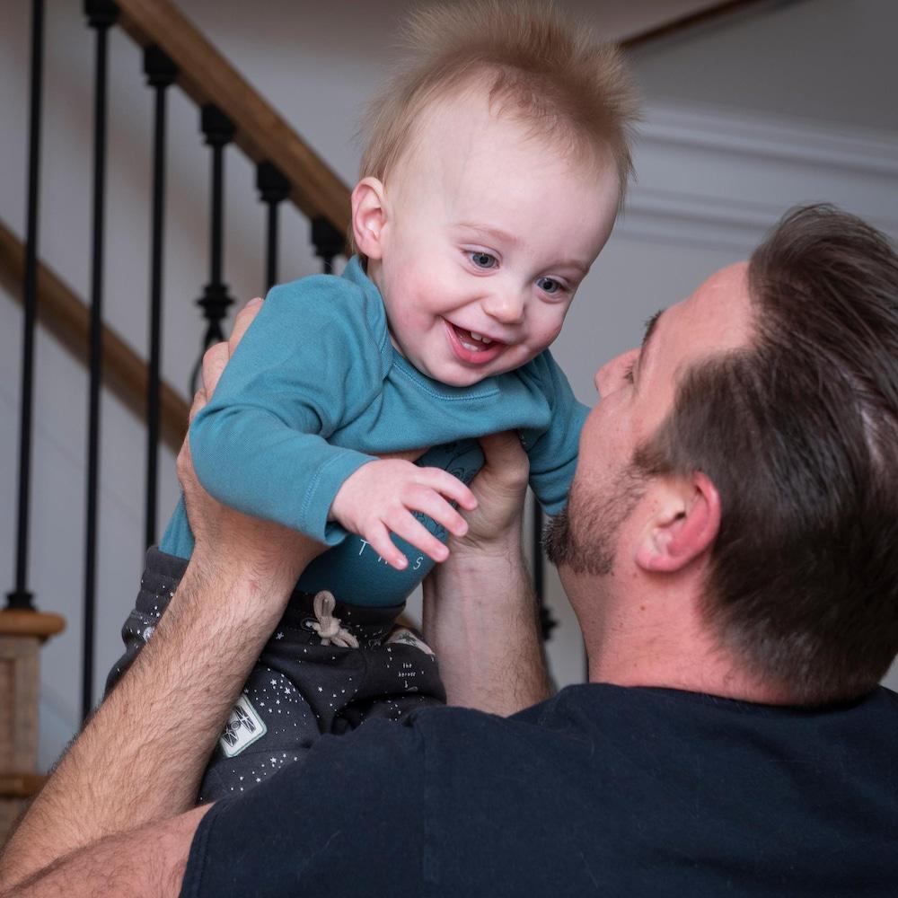 Le petit Aidan dans les bras de son père.