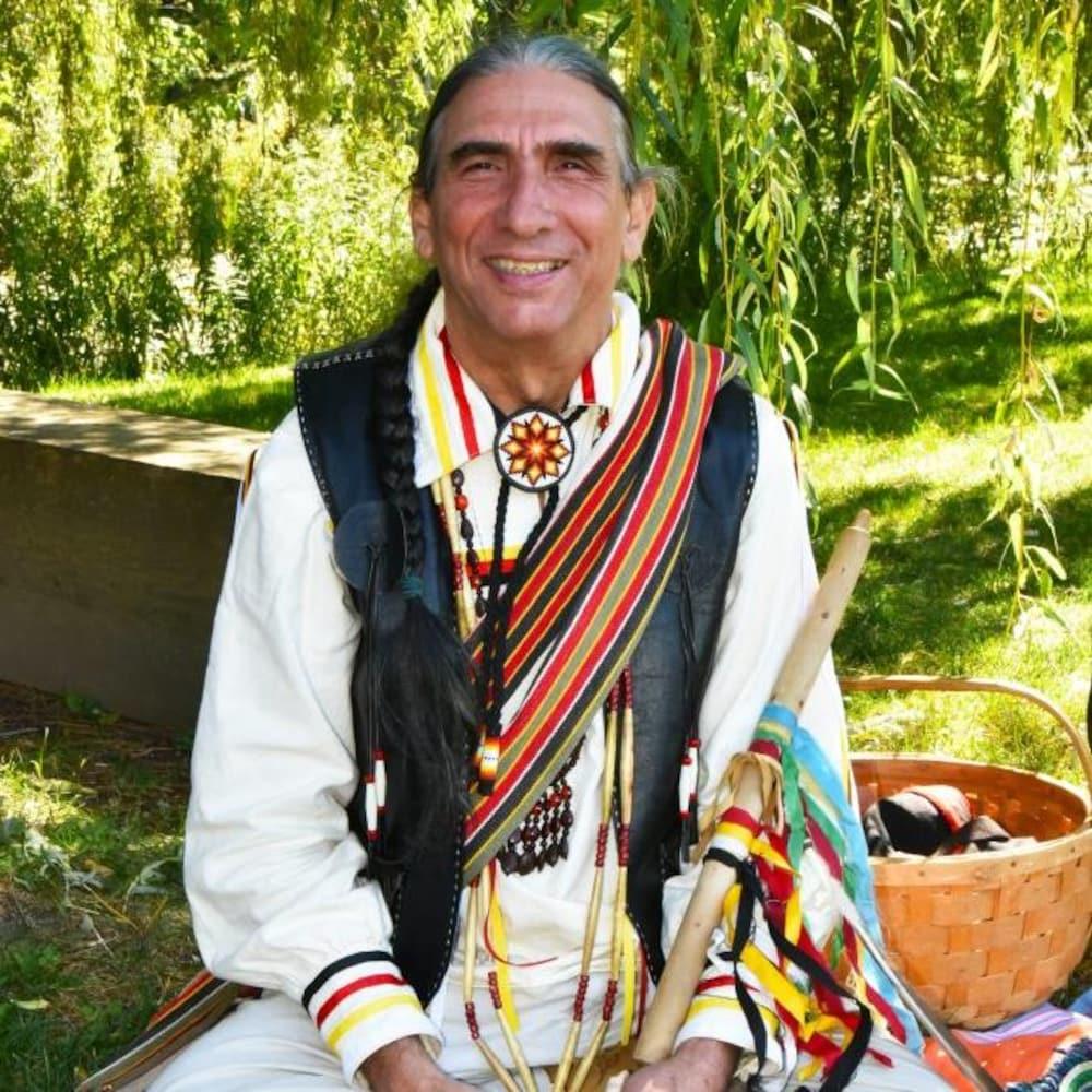Luc Bourgault, assis dans la pelouse et souriant.