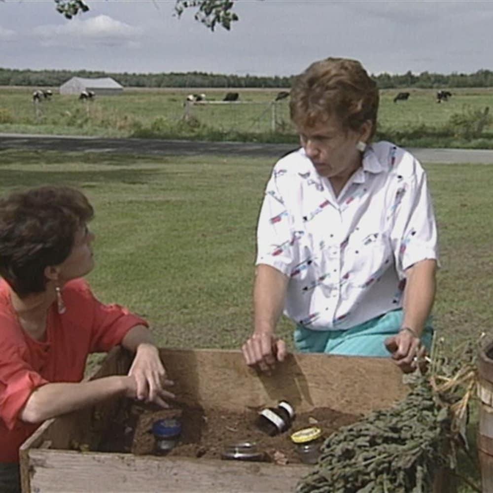 Deux femmes discutent devant un bac rempli de terre.