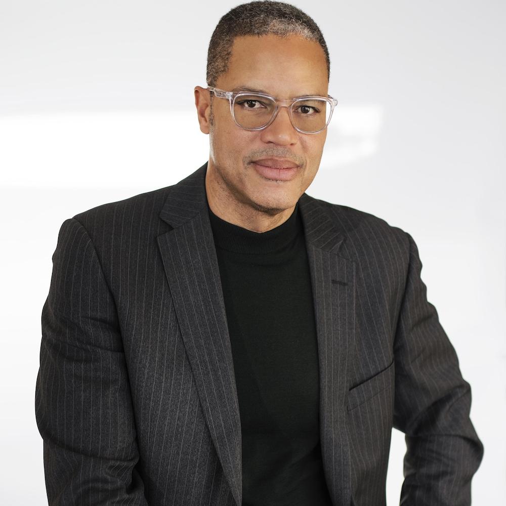Un homme noir, avec des lunettes translucides, assis sur un banc devant un fond blanc, regarde la caméra en souriant.