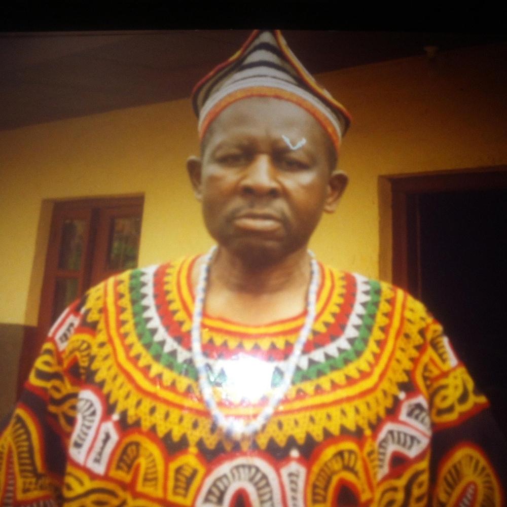 Le père d'Eric Keunne fronce les sourcils en regardant la caméra. Il porte une tenue traditionnelle africaine.
