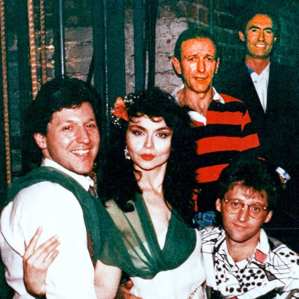 Andy Nulman, Gilbert Rozon et sept humoristes sourient dans les coulisses d'une salle de spectacle.
