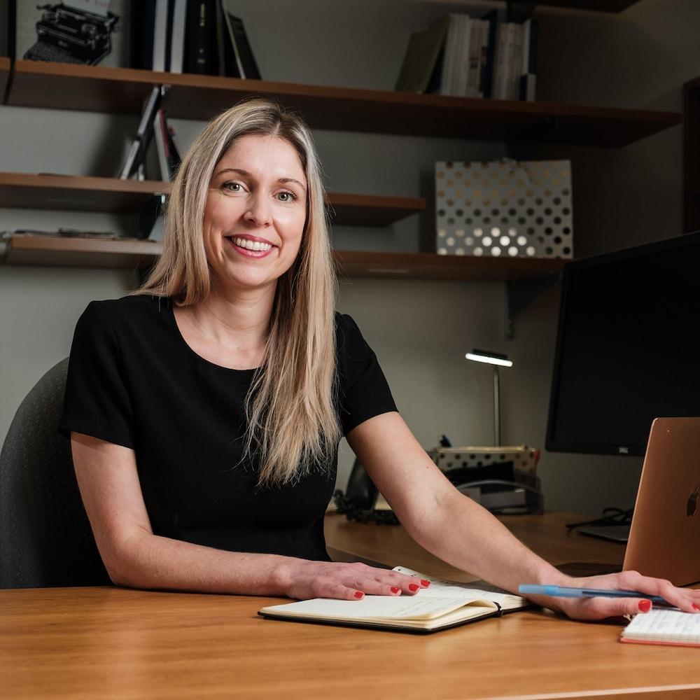 Marie-Ève Carignan assise à un bureau.