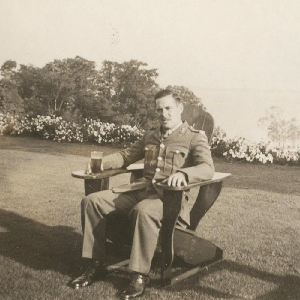 Un homme en uniforme assis sur une chaise en bois à l'extérieur.