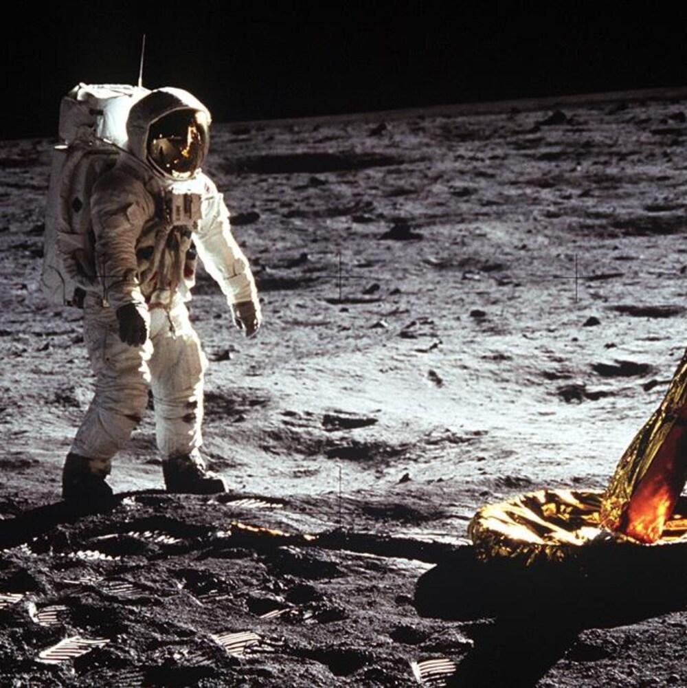 L'astronaute Buzz Aldrin marche sur la surface lunaire près de l'une des pattes du module.