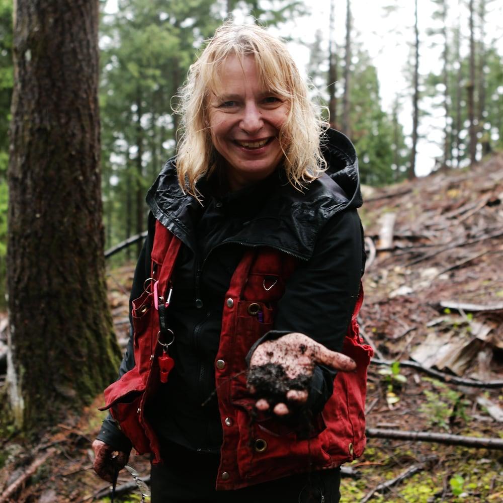 Une femme dans une forêt nous montre de la terre
