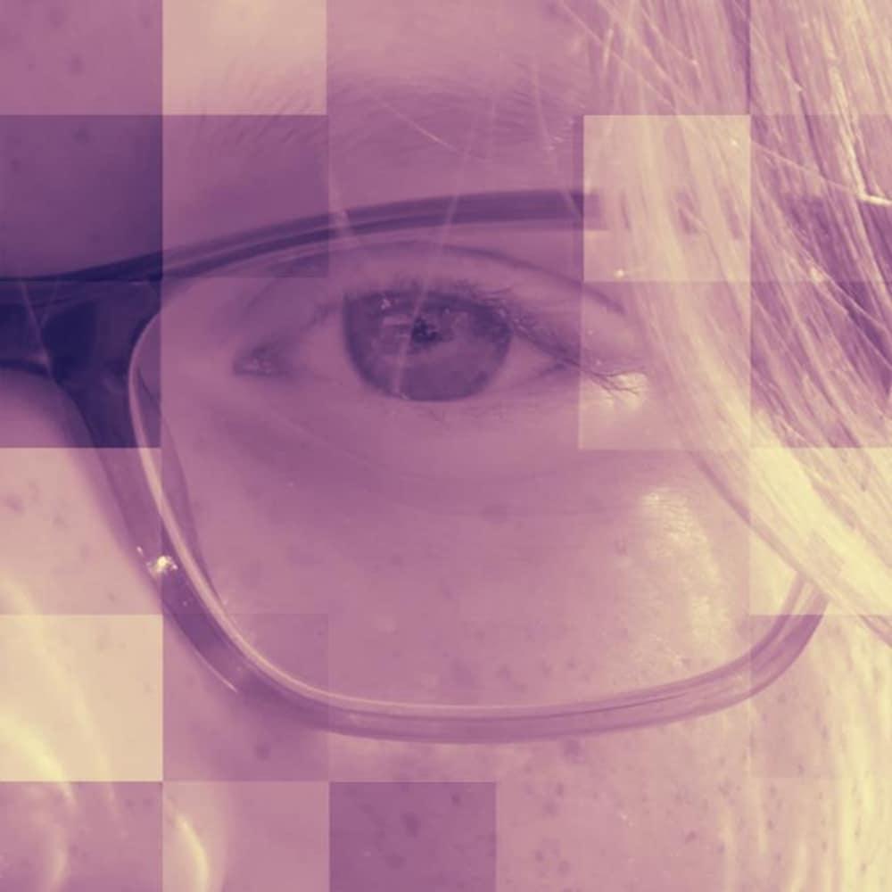 Un oeil entouré par une lunette recouverte par des cheveux longs.