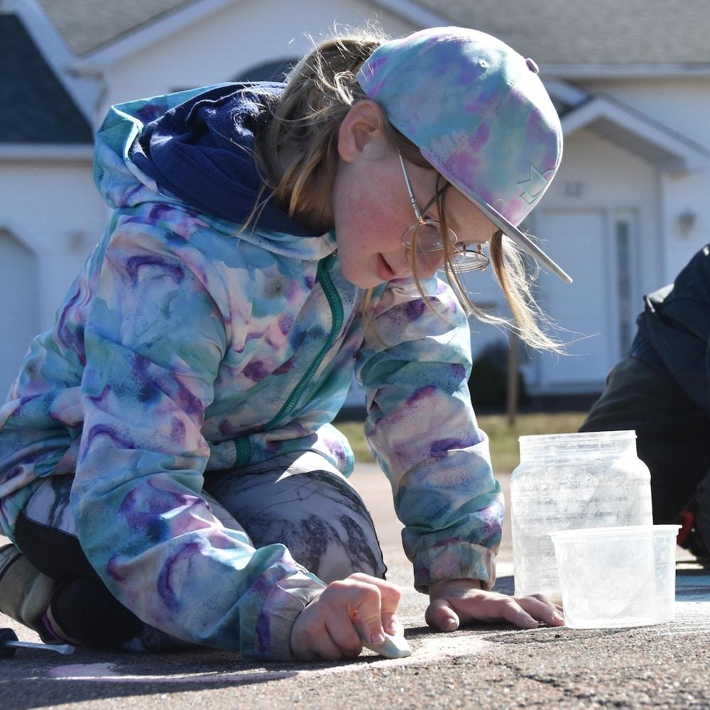 Maya et Sébastien qui dessinent à la craie sur le pavé d'un stationnement.