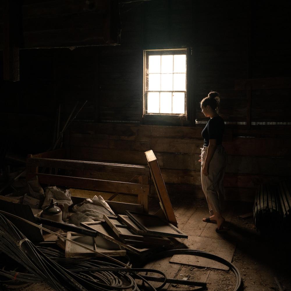 Ariane se tient près d'une fenêtre éclairant faiblement le deuxième étage de la grange centenaire, ou traînent de vieilles fenêtres.