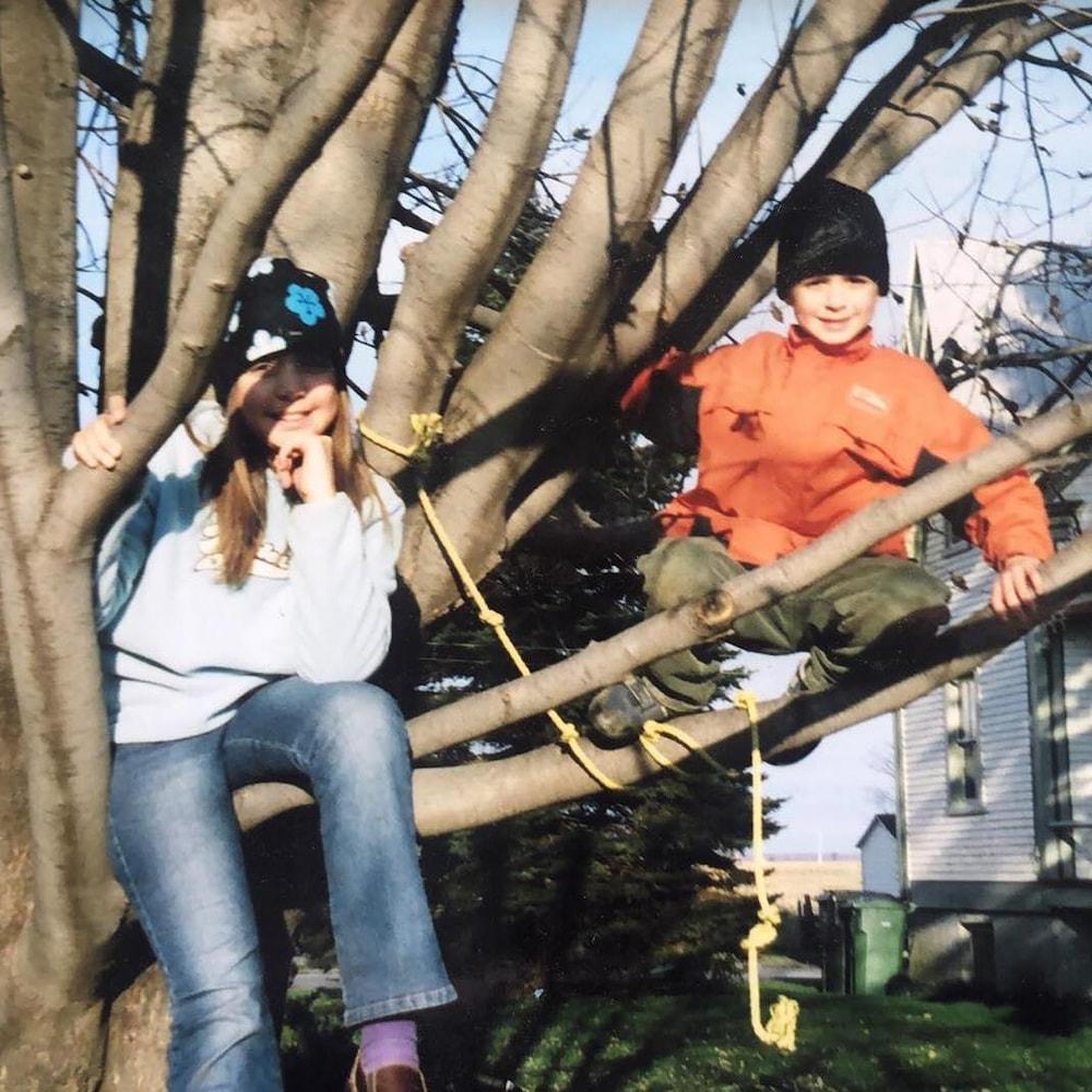 Ariane et Thomas-Louis sont assis dans les branches d'un grand arbre. À l'arrière-plan se dessine la maison familiale.