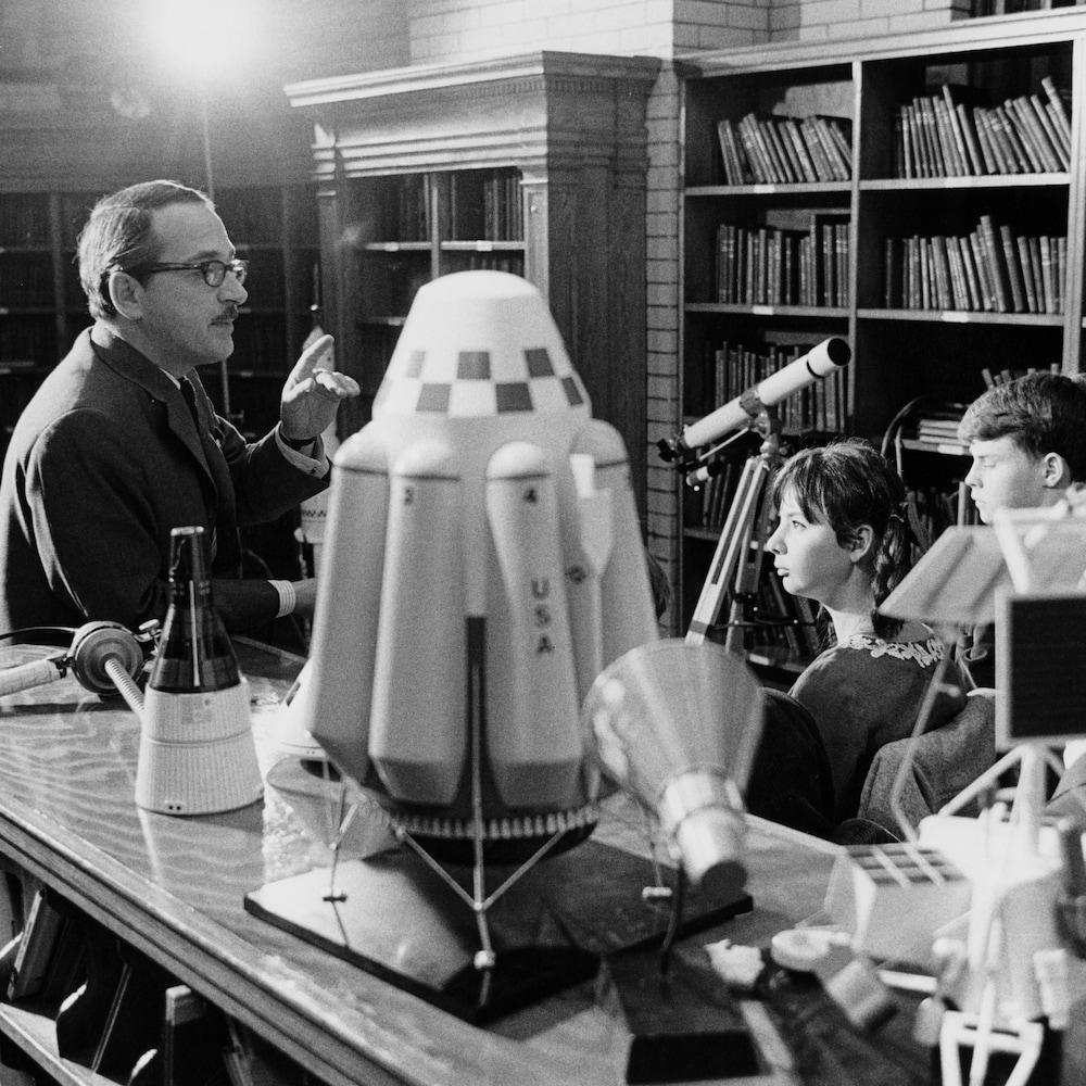 Jeunes qui écoutent Raymond Charette dans une bibliothèque, une maquette du fusée et un télescope sont placés sur une table.
