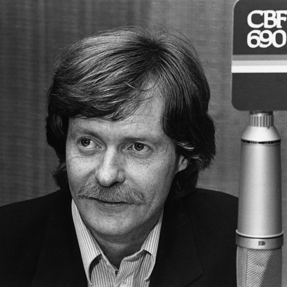 Yves Quenneville derrière un micro avec l'inscription CBF 690.