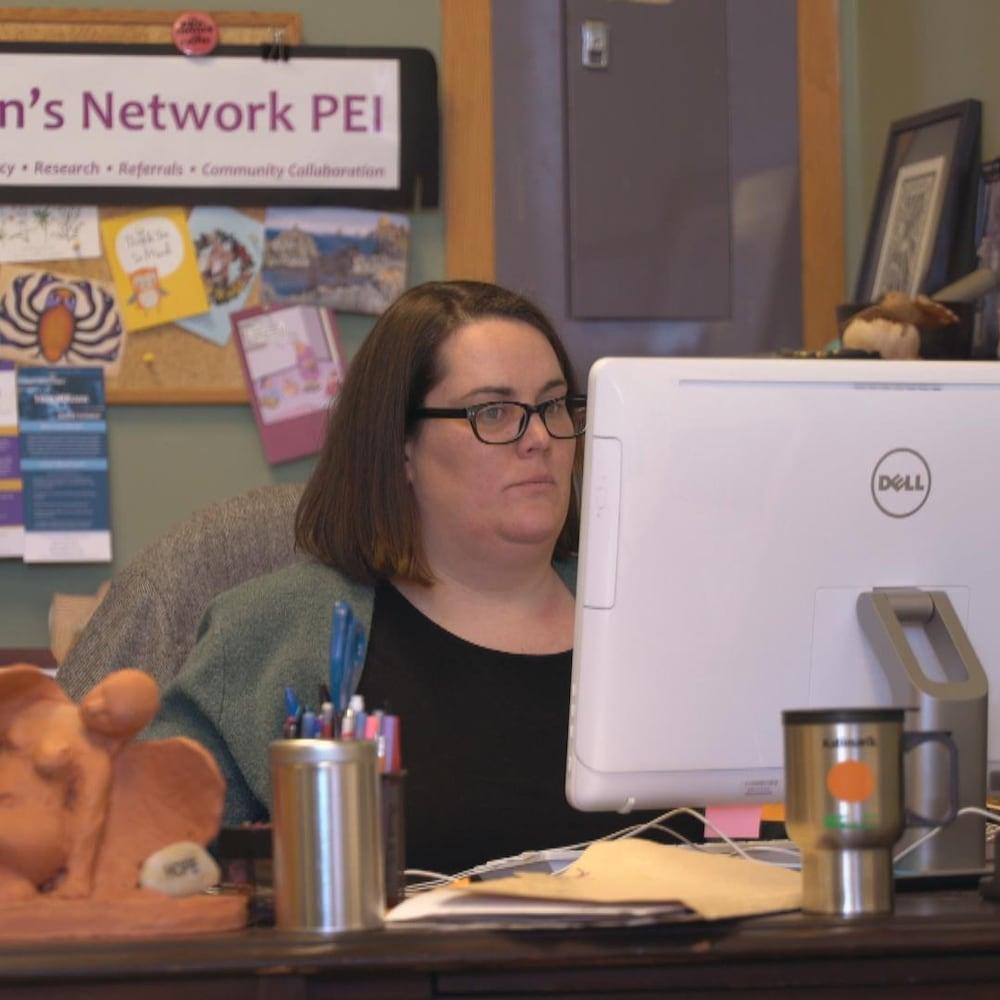 Une femme qui travaille à son ordinateur dans un bureau.