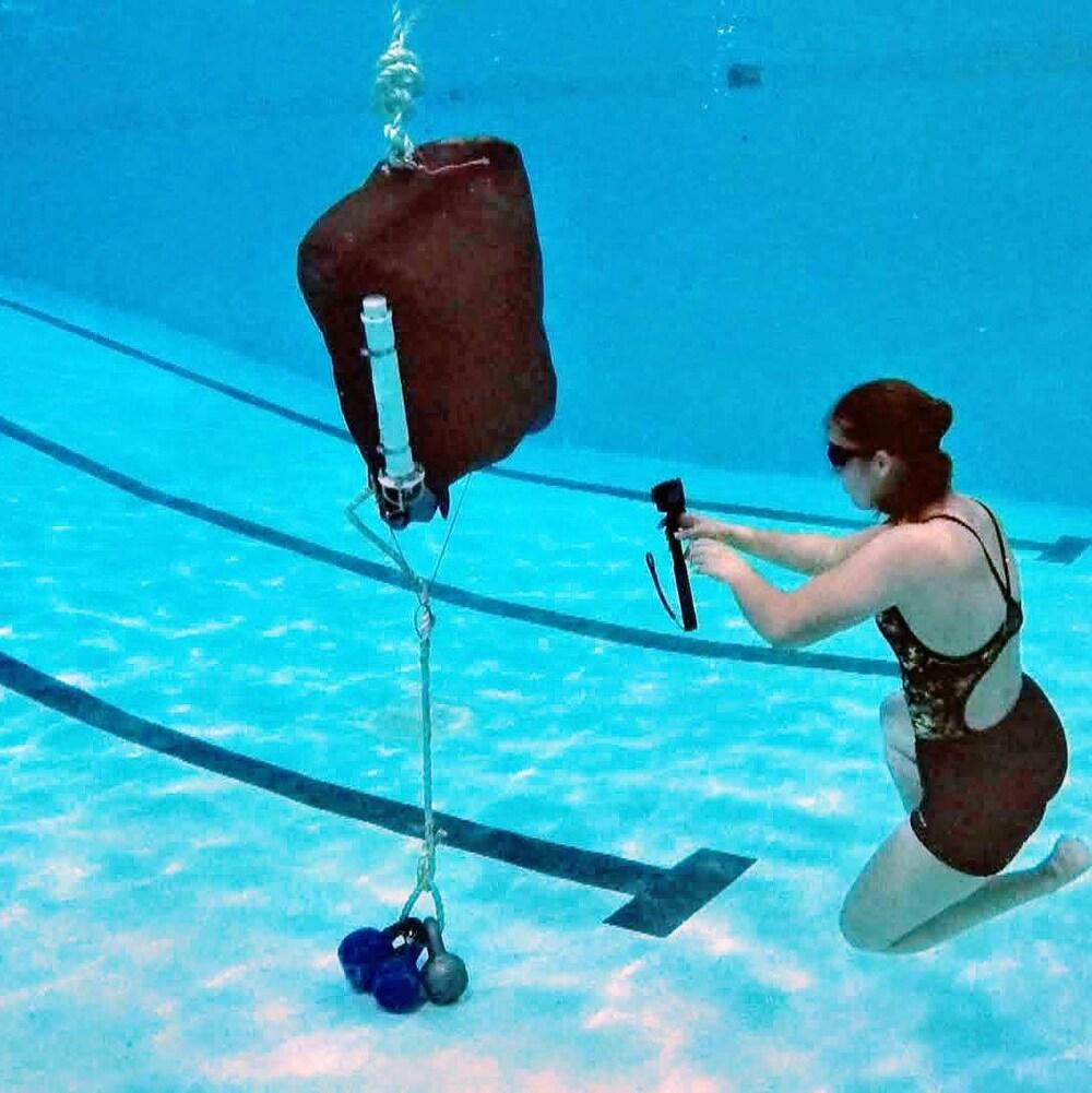 Une personne qui filme un engin de pêche dans une piscine.