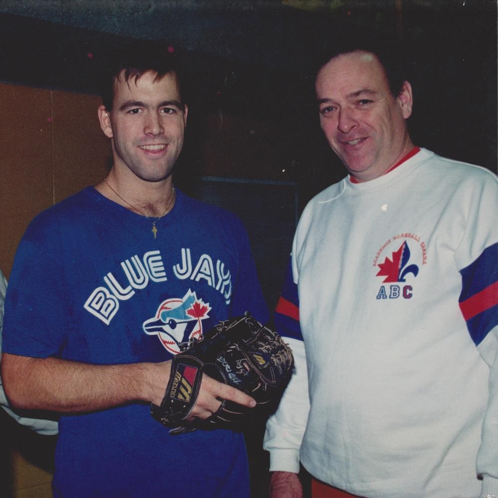 Les deux hommes sourient. L'un d'eux tient un gant de baseball.