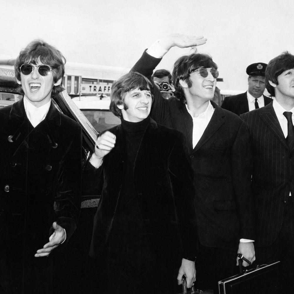 Les quatre membres du groupe The Beatles qui saluent leurs admirateurs et admiratrices en route vers l'aéroport de Boston, le 12 août 1966.