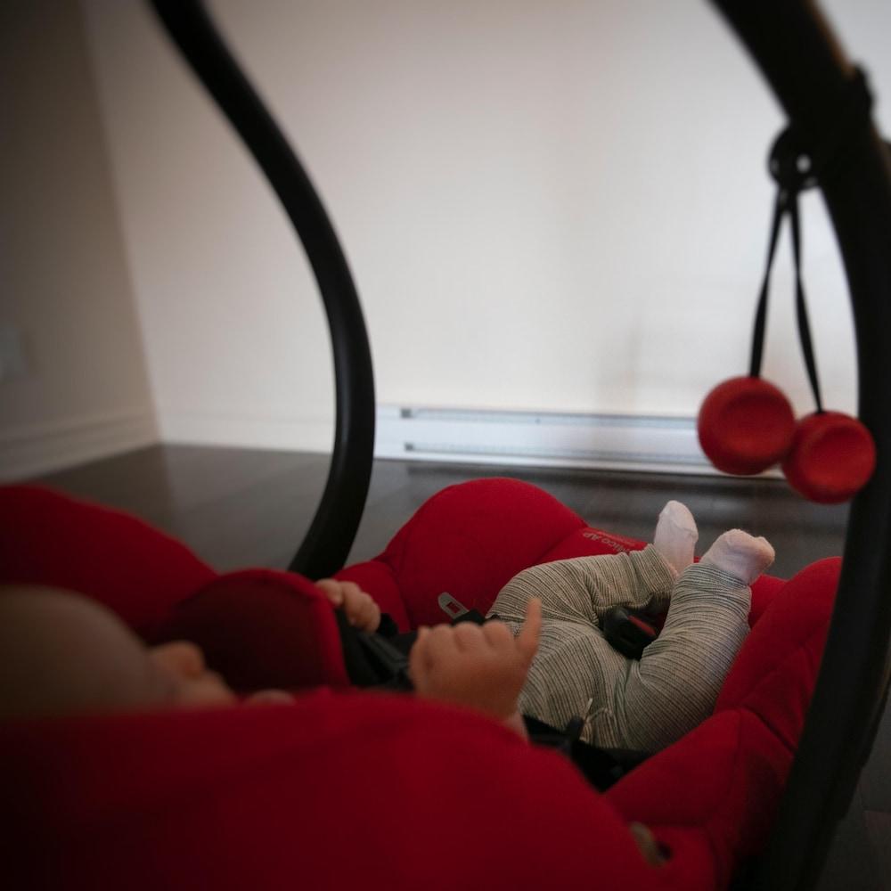 Un bébé dans son fauteuil, vu de profil, le petit doigt en l'air.
