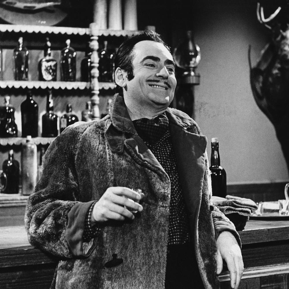 Guy Provost qui joue Alexis. Il boit un verre à l'hôtel.