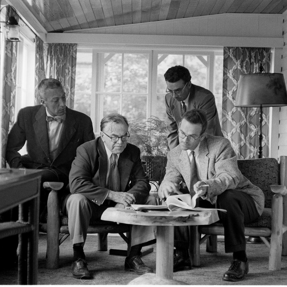 Claude-Henri Grignon et François Quirion regardent des textes sur une véranda, deux autres hommes sont avec eux.