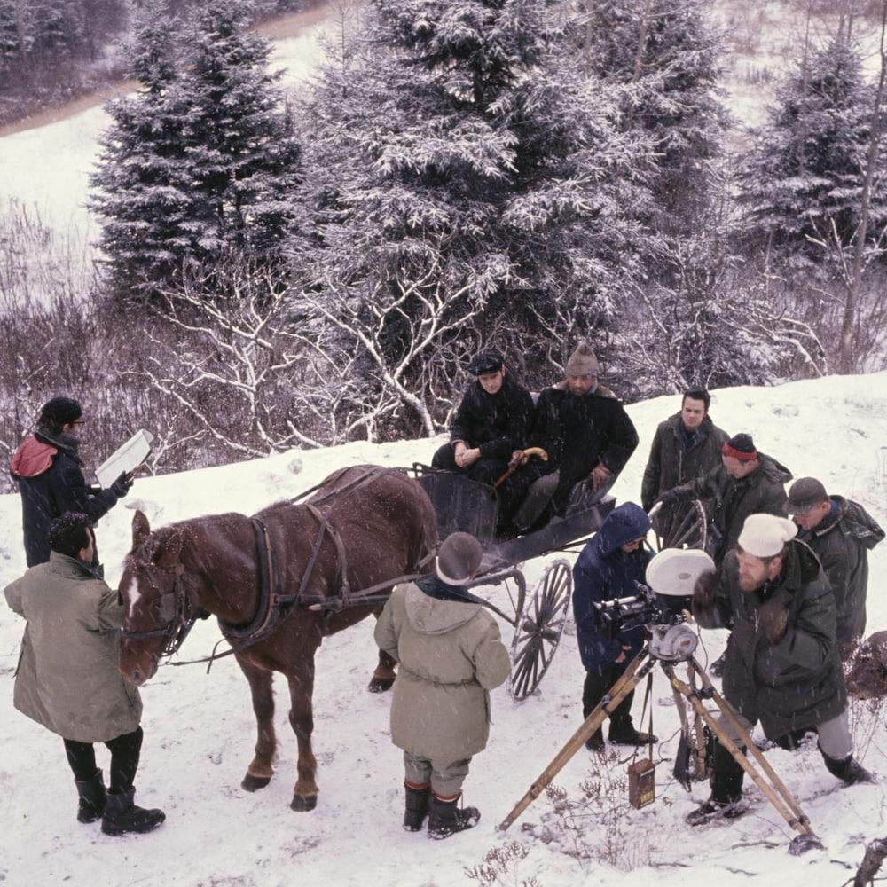 Équipe de tournage techniciens, caméraman, réalisateur et deux hommes dans une calèche, neige au sol.