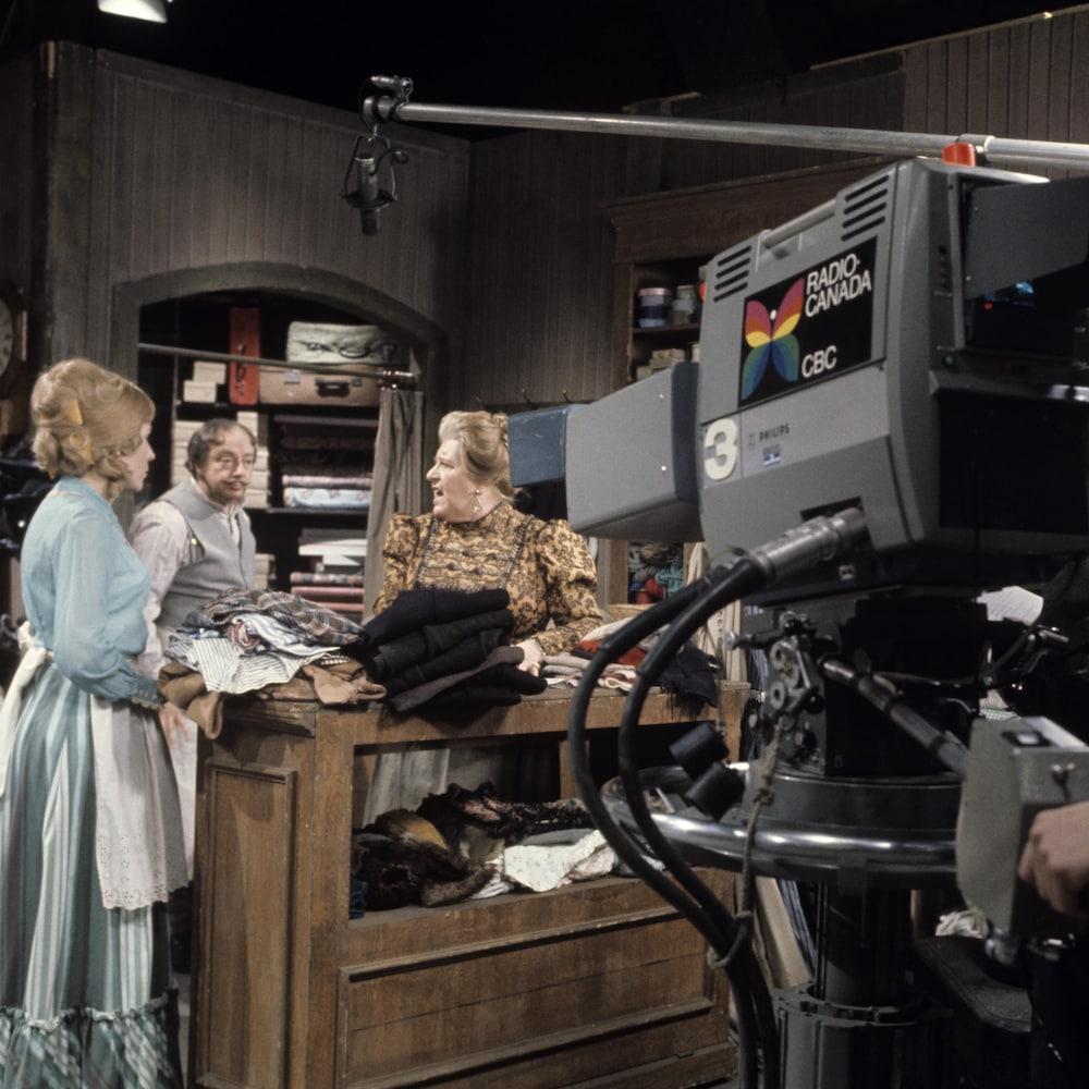 Scène de tournage au magasin général dans « Les belles histoires des pays d'en haut », caméraman et comédiens au travail.
