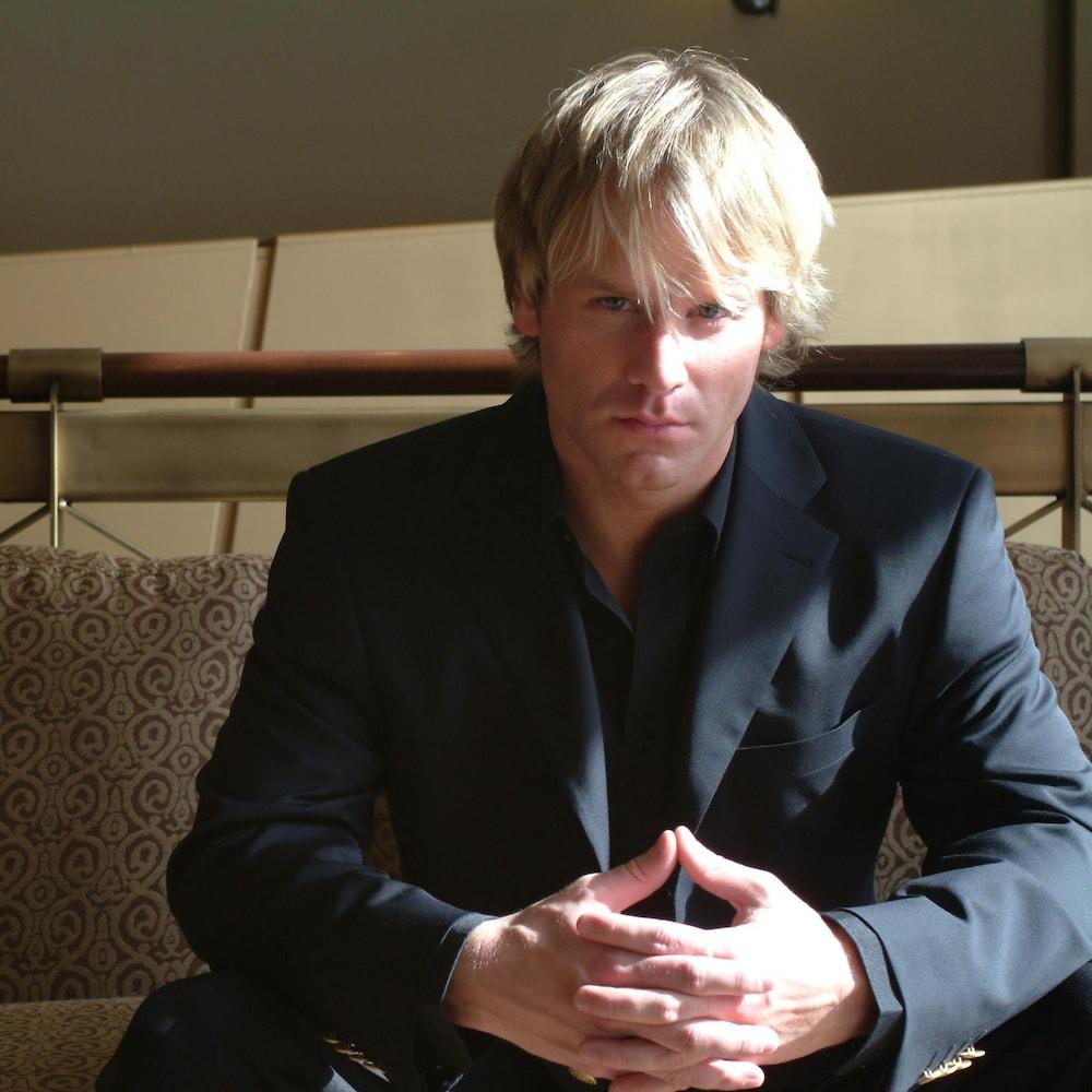 Bernard Lachance assis sur un divan.