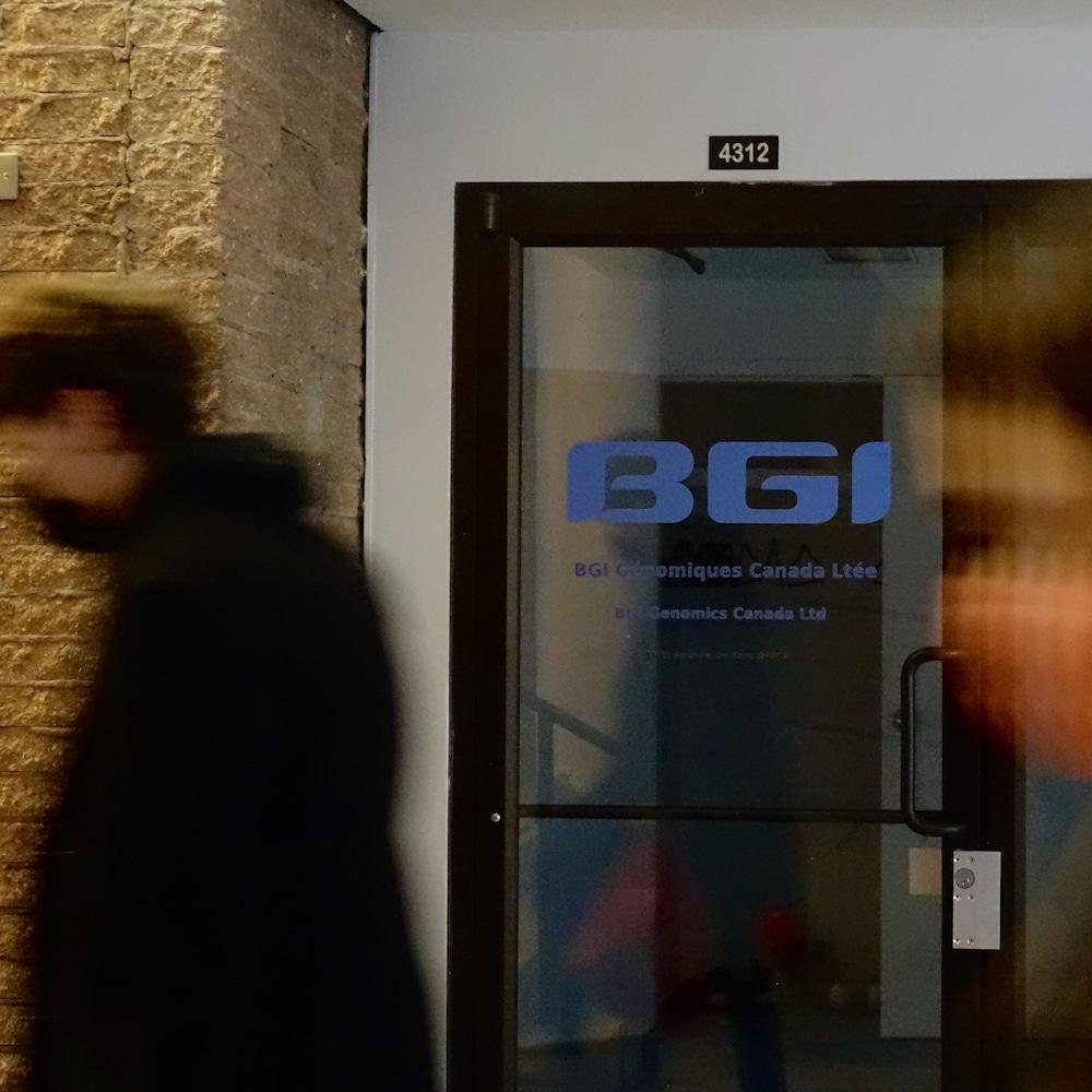 Deux personnes passent devant les locaux de BGI sur l'avenue du Parc, à Montréal.