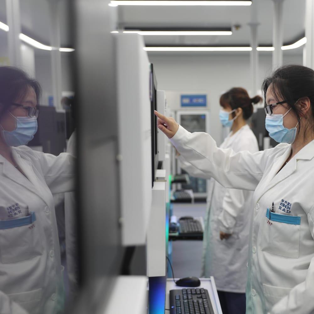 Une chercheuse de BGI devant un séquenceur d'ADN.