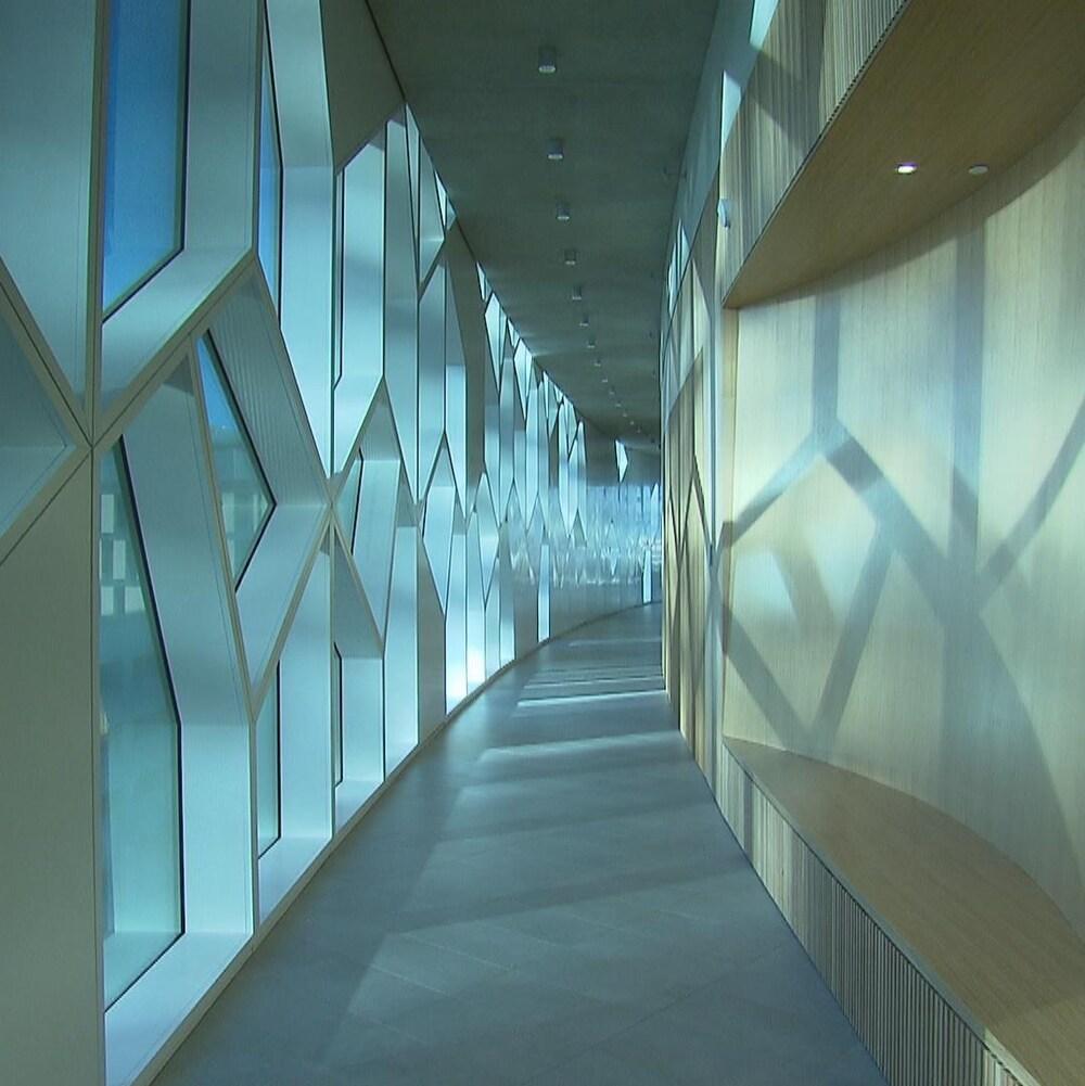 Un couloir de la bibilothèque avec un mur en bois à droite et des fenêtres donnant sur le centre-ville à gauche.
