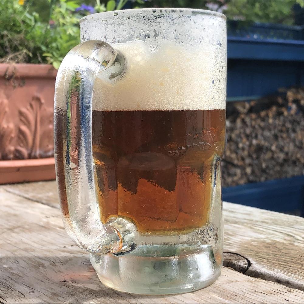 Un bock de bière suintant au soleil par un bel après-midi d'été.