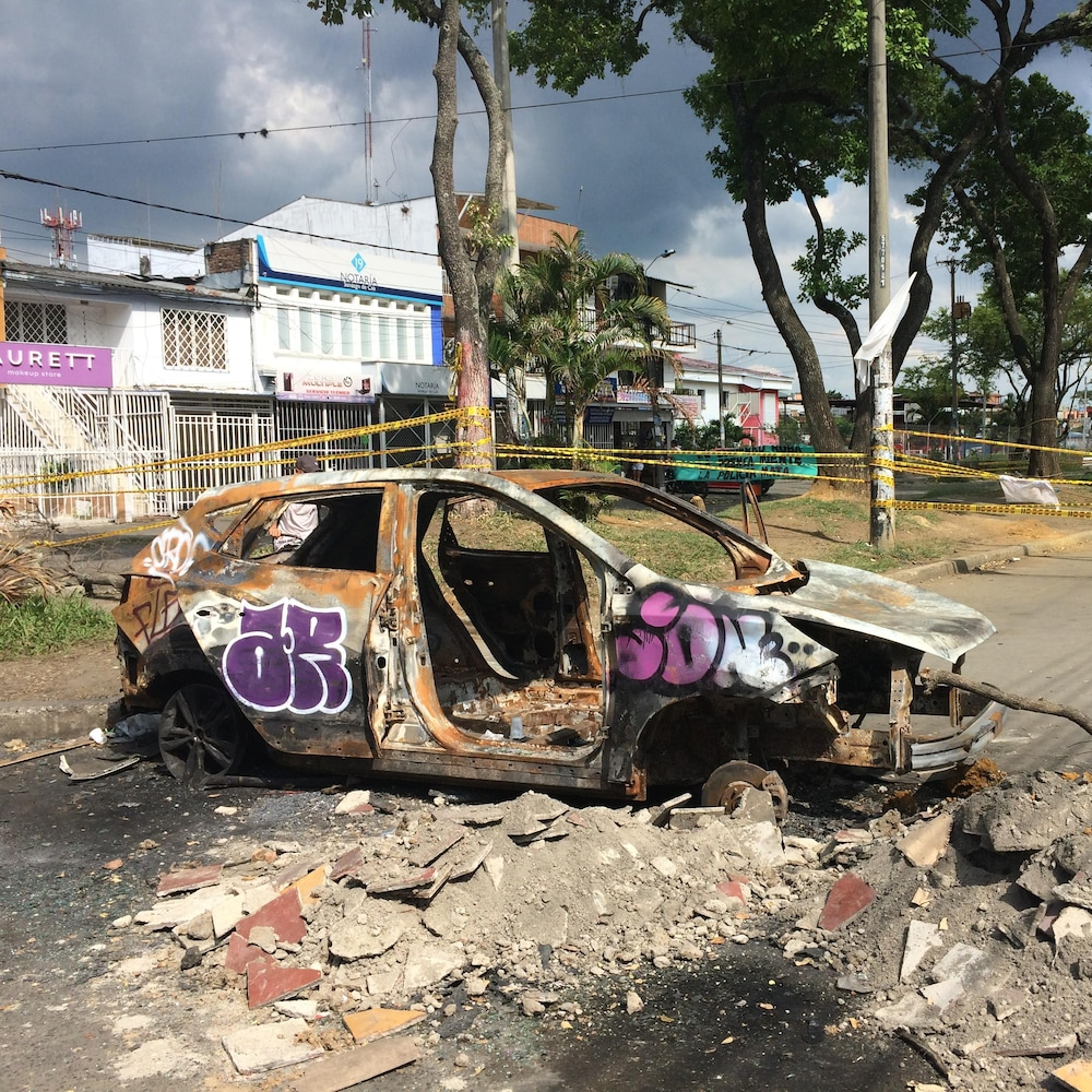 Une voiture brûlée entourée de gravats marque l'entrée de Puerto Resistencia.