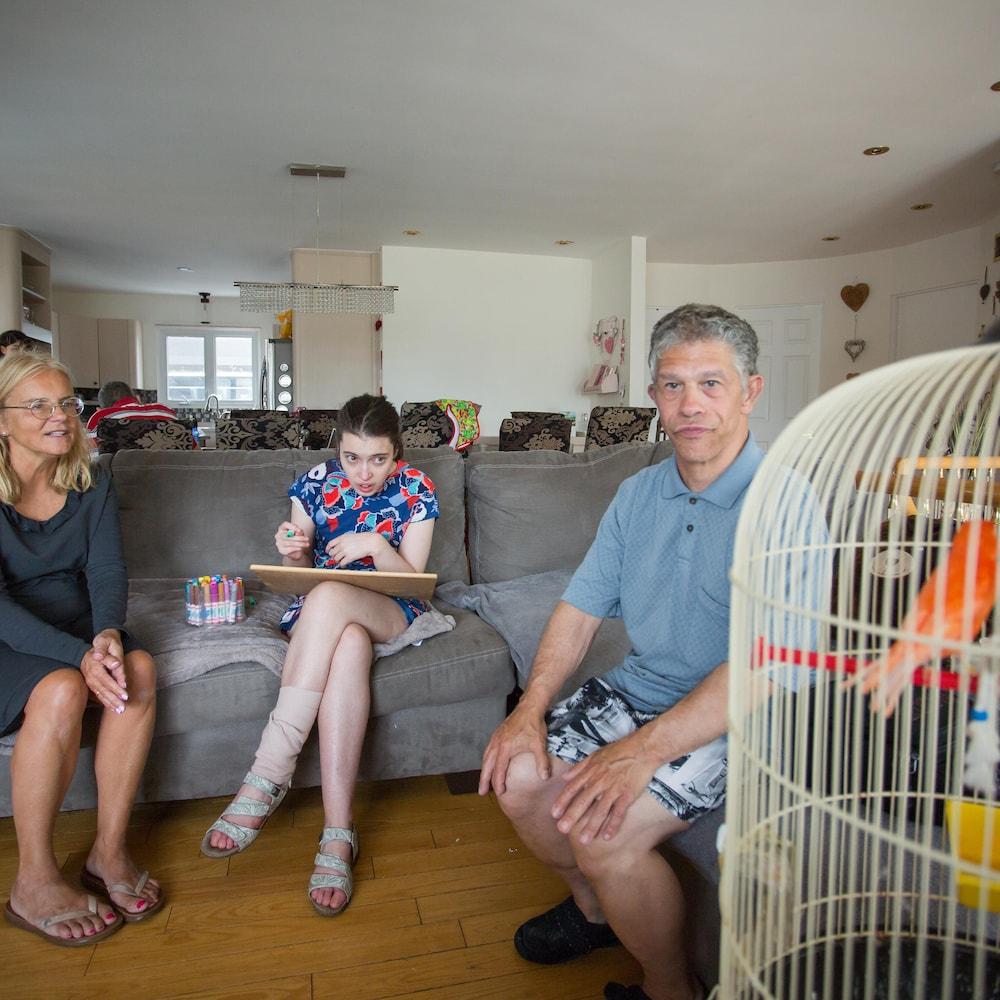 Lucie, Camélia et Danny, accompagnés de l'un des trois oiseaux de la maison de répit.