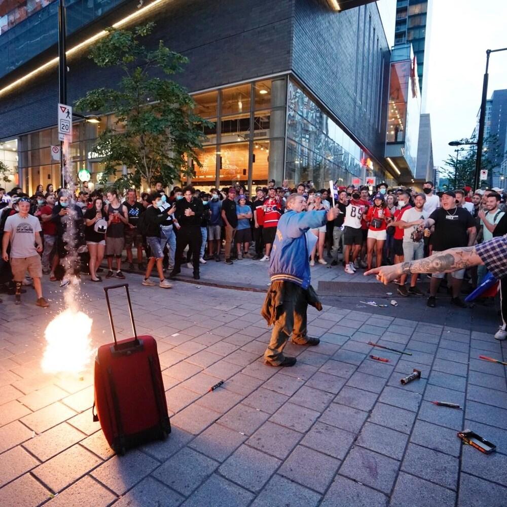 Une foule près du Centre Bell autour de pétards créant des flammes.