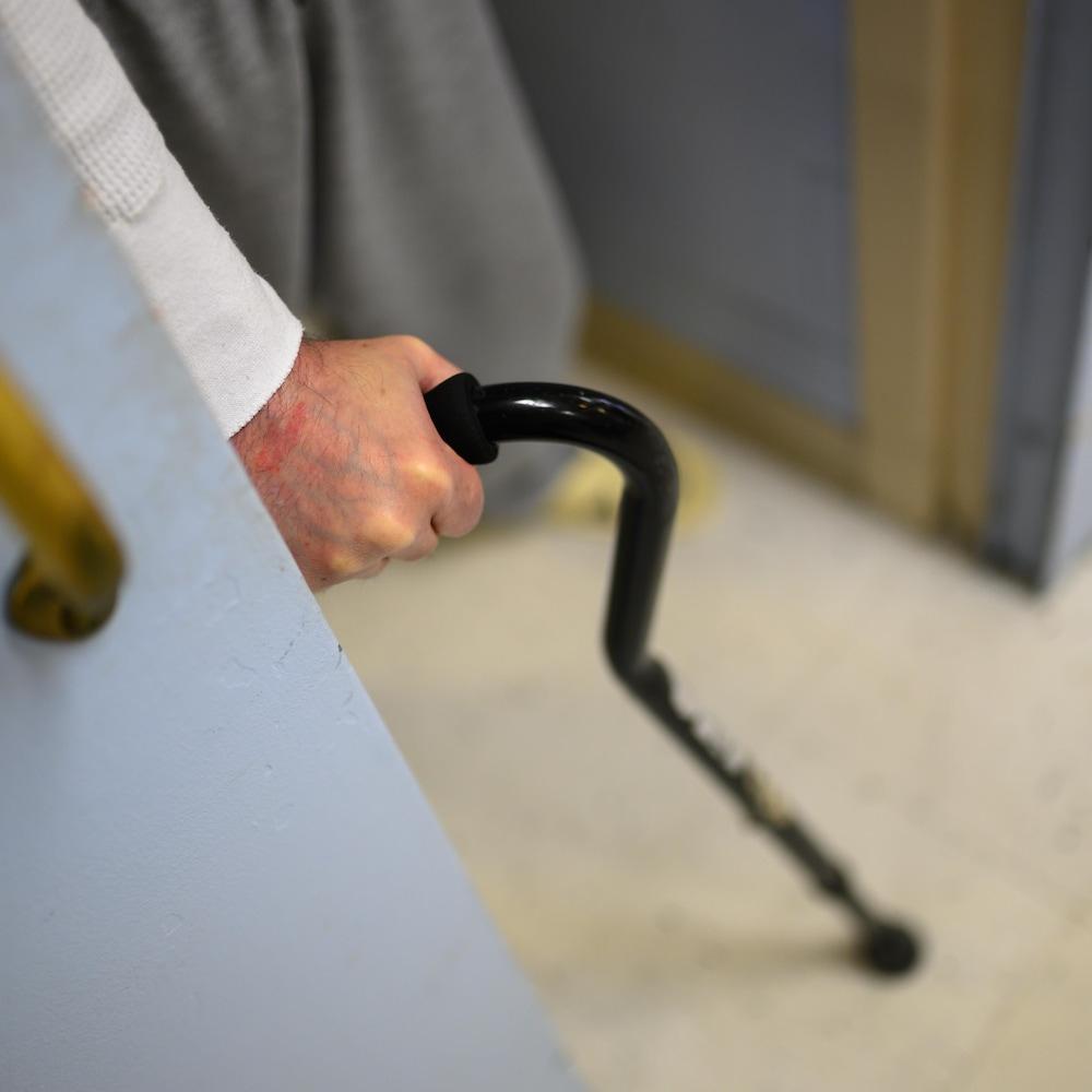 Un détenu sort de sa cellule à l'aide du canne.
