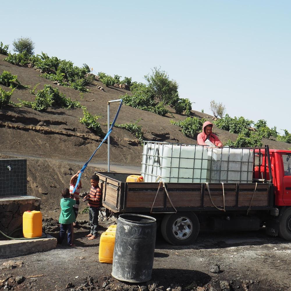 Un homme remplit des cuves d'eau alors que des gamins s'amusent à côté du camion.